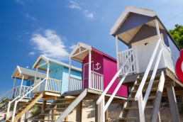 looking up to a row of colourful beach huts under a blue sky at wells next the sea beach in norfolk self catering | sextons place